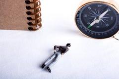 Man, kompass och spiralanteckningsbok Royaltyfria Bilder