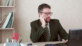 Man kontorsarbetaren med ett skägg och exponeringsglas som talar till en klient på en smartphone arkivfilmer