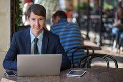 Man kopplade av den unga stiliga yrkesmässiga affärsmannen som arbetar med hans bärbar dator, telefon och minnestavla i ett bullr Arkivfoton