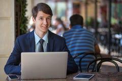 Man kopplade av den unga stiliga yrkesmässiga affärsmannen som arbetar med hans bärbar dator, telefon och minnestavla i ett bullr Royaltyfri Foto