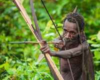 Man Korowai tribe shoots a bow. Tribe of Korowai Kombai , Kolufo. Royalty Free Stock Photos
