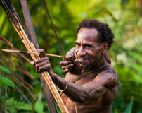 Man Korowai tribe shoots a bow. Tribe of Korowai Kombai , Kolufo. Stock Photo