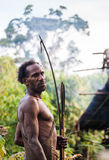 Man Korowai tribe shoots a bow. Tribe of Korowai Kombai , Kolufo. Royalty Free Stock Photography