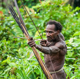 Man Korowai tribe shoots a bow. Tribe of Korowai Kombai , Kolufo. Royalty Free Stock Photo