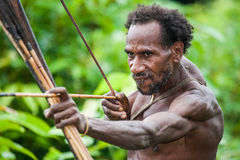 Man Korowai tribe shoots a bow. Tribe of Korowai Kombai , Kolufo. Royalty Free Stock Images