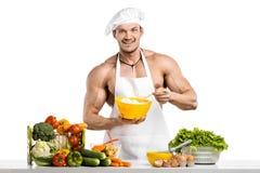 Man kroppsbyggaren i vit toqueblanche och laga mat det skyddande förklädet royaltyfri bild