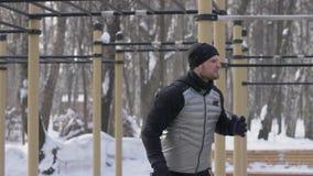 Man kroppsbyggareutbildning med konditionutrustning på vintersportjordning stock video
