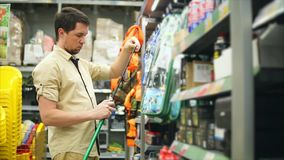 Man kunden som väljer metspön i lagret för att fiska Honom som tar stången arkivfilmer