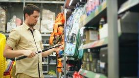 Man kunden som väljer metspön i lagret för att fiska Honom som tar stången stock video