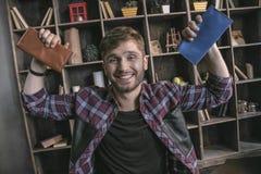 Man läderproducenten som ler och rymmer den två avslutade läderhandväskan arkivbild