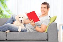Man läseboken och att ligga på soffan med en hund Royaltyfri Foto