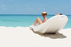 Man lögnen på den sunbed dagdrivaren och dricka kokosnötcoctailen på strandwi royaltyfria bilder