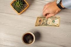 Man& x27; la mano de s da un billete de dólar 10 en el pago para una taza de café Fotografía de archivo libre de regalías