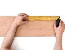 Man& x27; la s passa la plancia di legno di misurazione con un righello del ferro, isolato su fondo bianco immagine stock libera da diritti