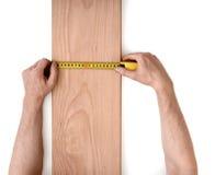 Man& x27; la s passa la plancia di legno di misurazione con una linea del nastro isolata su fondo bianco immagine stock