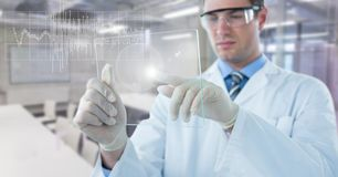 Man in lab coat with glass device and white graph with flare against blurry lab Royalty Free Stock Photos