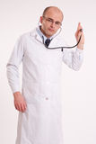 Man in lab coat listening through a stethoscope Royalty Free Stock Image