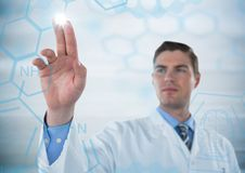 Man in lab coat pointing at blue medical interface with flare against grey background Royalty Free Stock Photos
