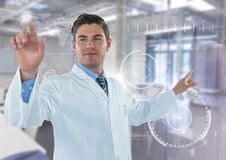 Man in lab coat pointing with flare against white interface and blurry lab Stock Image