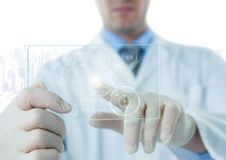 Man in lab coat pointing at white interface and flare on glass device against white skyline Royalty Free Stock Image