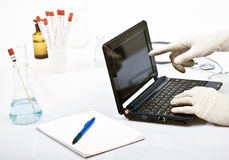 Man in laboratory. Man doing research in laboratory, taking samples, writing in agenda and using laptop for researcg Royalty Free Stock Photos