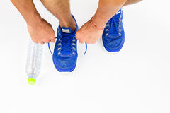 Man lacing sport shoes with water bottle on white background stock image
