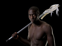 Man with a lacrosse stick over his shoulder. A buff shirtless handsome black man with a mens lacrosse stick over his shoulder, turns and looks into the camera Royalty Free Stock Image