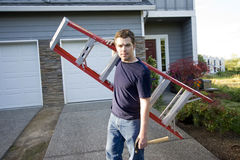 Man with Ladder. Man with a serious look on his face standing in front of house holding ladder and hammer. Horizontlly framed photo stock images