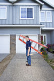 Man with Ladder. Smiling man standing in front of house holding ladder and hammer. Vertically framed photo stock images