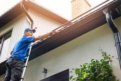 Man on ladder cleaning house gutter. From leaves and dirt Stock Photo