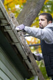 Man Cleaning Gutter. A man is on a ladder cleaning out the dirty gutter. shallow depth of field. focus on hand in gutter Royalty Free Stock Images