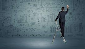 Man on ladder drawing charts Stock Photos