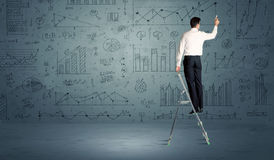 Man on ladder drawing charts Stock Photos