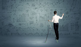 Man on ladder drawing charts Royalty Free Stock Images