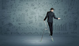 Man on ladder drawing charts. A businessman in modern stylish elegant suit standing on a small ladder and drawing pie and block charts on grey wall background Stock Photography