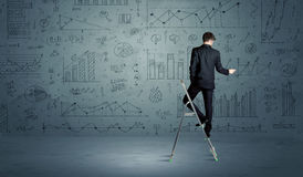 Man on ladder drawing charts Royalty Free Stock Photography