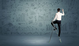 Man on ladder drawing charts Royalty Free Stock Image