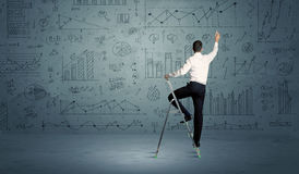 Man on ladder drawing charts Stock Image