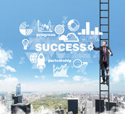 A man in a ladder is drawing some business diagram in the air as a concept of success Stock Images