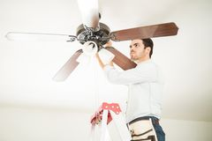 Man in ladder fixing ceiling fan. Portrait of a busy handyman standing on a ladder and fixing a ceiling fan in a house Stock Photos