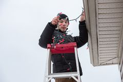 Man climbing a ladder to hang christmas lights outdoors. A Man on a ladder while hanging Christmas lights on the side of a home stock image
