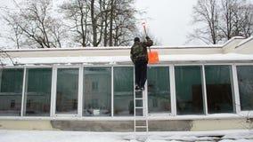 Man ladder orange shovel tool clean snow greenhouse roof winter