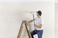 Man on ladder with paint roller Royalty Free Stock Photo