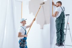 Home renovation crew. Man on the ladder and painter painting the wall. Home renovation crew concept Royalty Free Stock Image