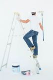 Man on ladder painting with roller Royalty Free Stock Photos