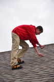 Man on Ladder on a roof. A roofer taking pictures of the layers of shingles on a home Stock Photography