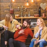 Man and ladies on happy faces discussing and drinking mulled wine. Friends spend leisure in cozy interior. Soulmates royalty free stock photo