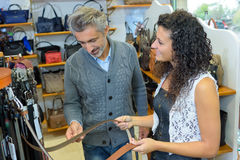 Man and lady looking at belts in shop Royalty Free Stock Photos