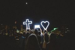 Man and Lady Raising Cross Heart Led Light Photo during Night Time Stock Photo