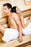 Man and lady sitting back to back in sauna Royalty Free Stock Photos